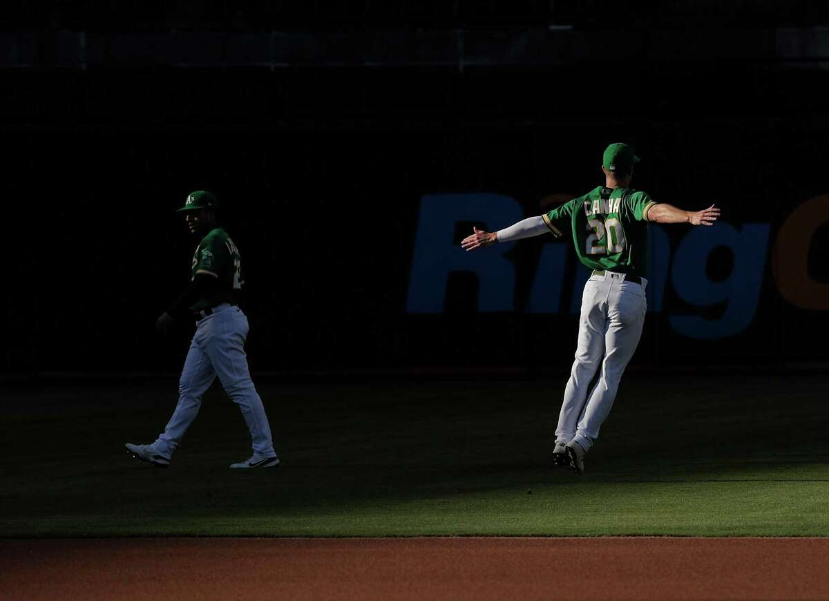 Mark Canha (20) stretches before the Oakland Athletics played the San Diego Padres at the Coliseum in Oakland, Calif., on Tuesday, August 3, 2021.