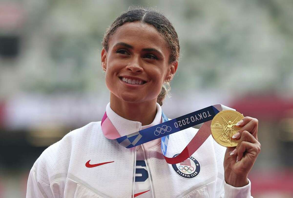 American runner Sydney McLaughlin displays her gold medal after breaking her own record in the 400-meter hurdles.
