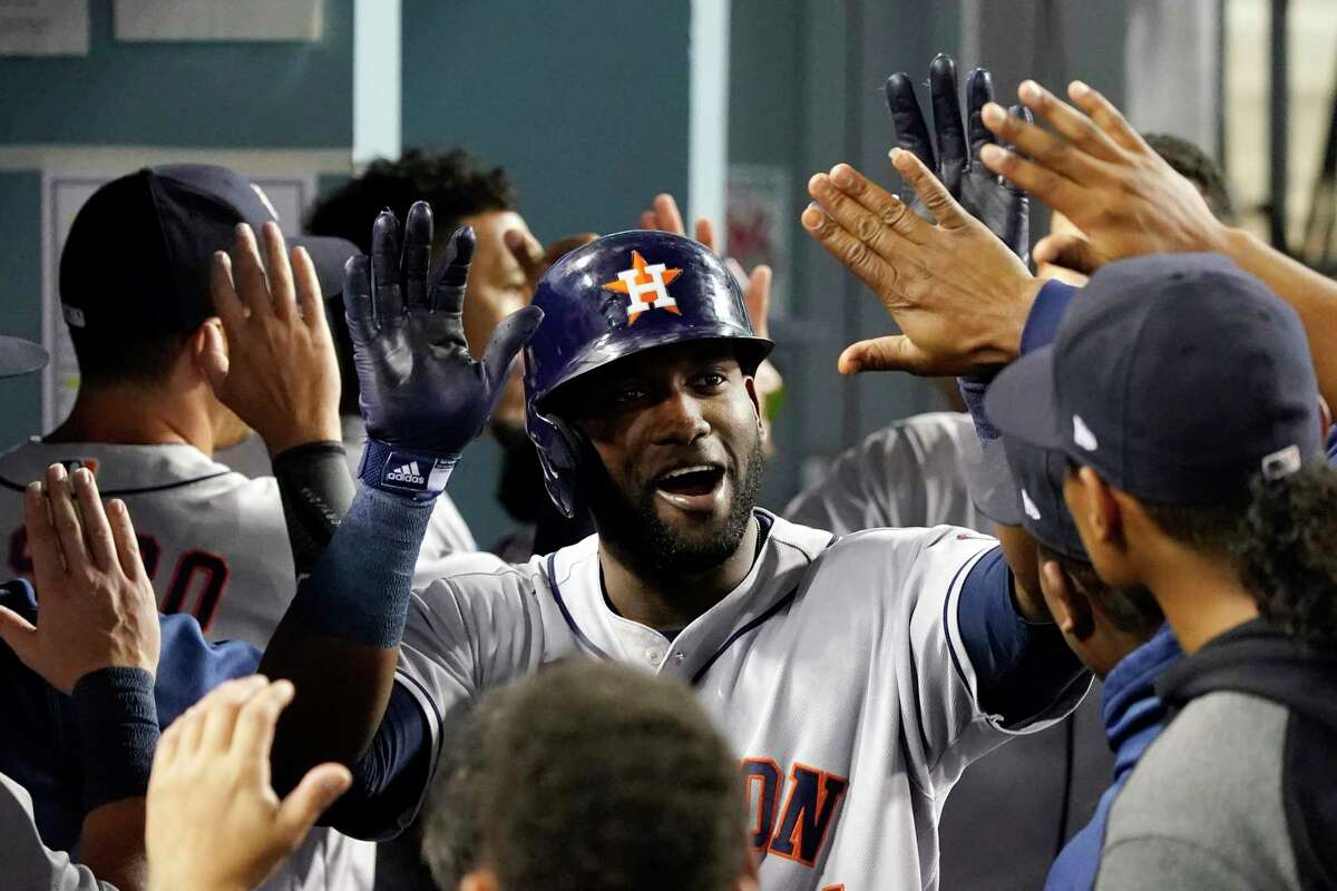 Houston Astros' Yordan Alvarez is congratulated for his two-run home run by teammates in the dugout during the eighth inning against the Los Angeles Dodgers on Tuesday, Aug. 3, 2021, in Los Angeles. (AP Photo/Marcio Jose Sanchez)