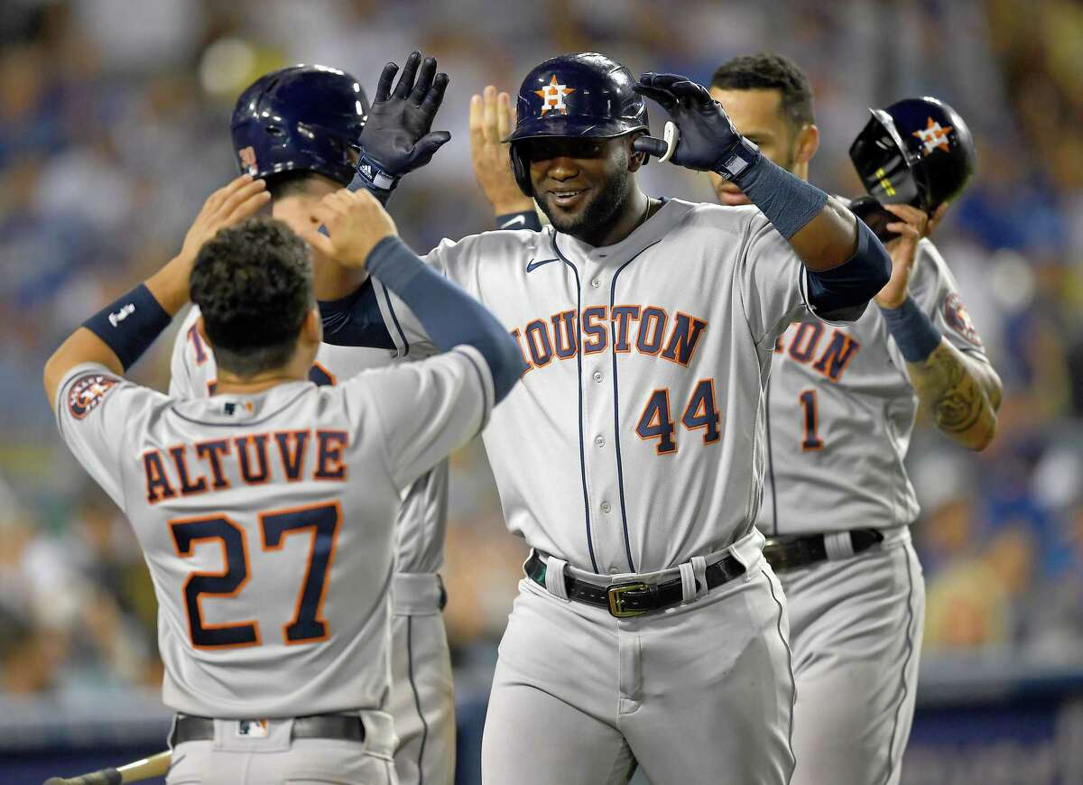 Yordan Alvarez #44 is greeted by Jose Altuve #27 of the Houston Astros after hitting a two-run home run in the eighth inning against the Los Angeles Dodgers at Dodger Stadium on August 3, 2021 in Los Angeles, California.