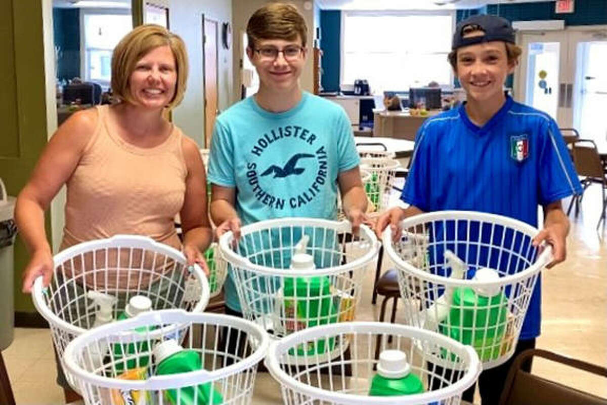 Main Street Community Center volunteer Jennifer Weber with her sons Aidan, left, and Max as they delivered laundry baskets and supplies to seniors last month as part of the Madison County CARES Grant program.