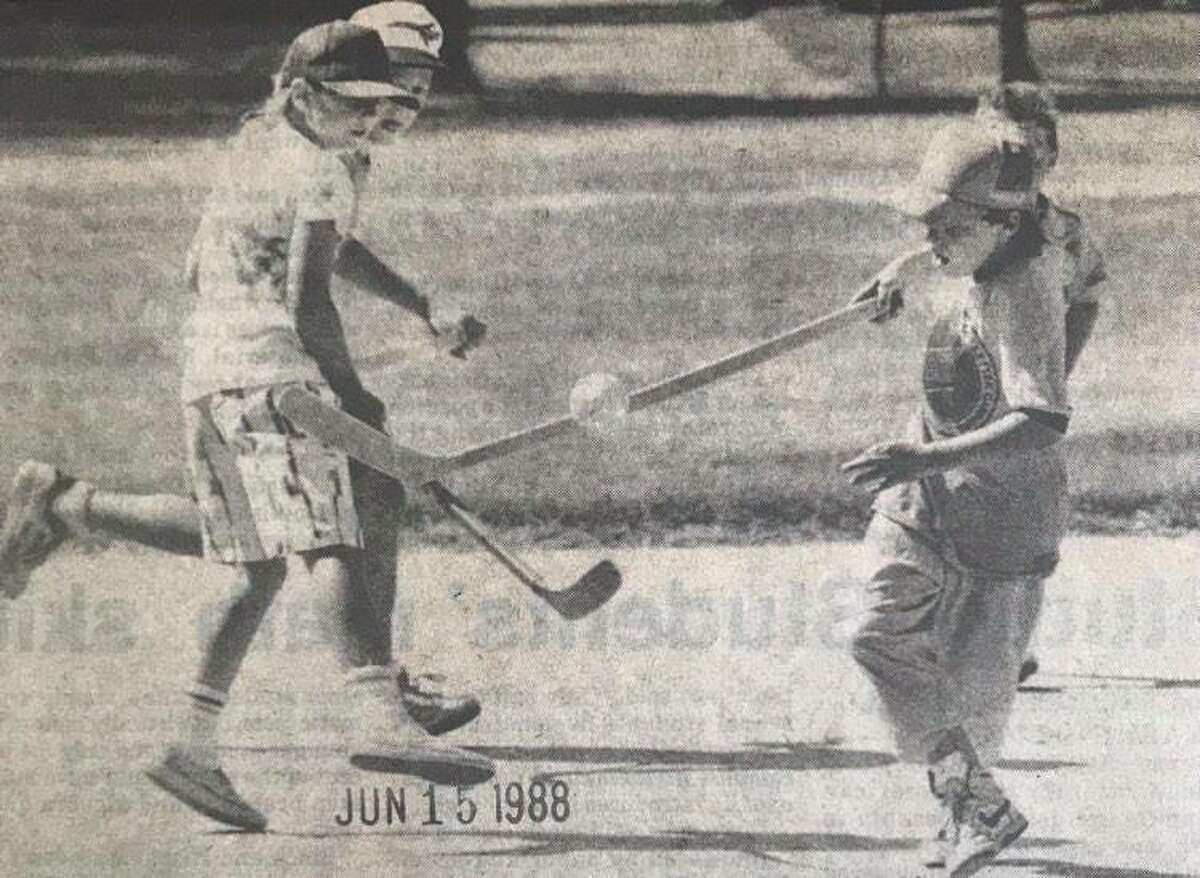 Gabe Paquet, 8, left, and Michael Scribner, 10, play a game of hockey at Carpenter School as part of the Midland Parks and Recreation playground program. June 1988