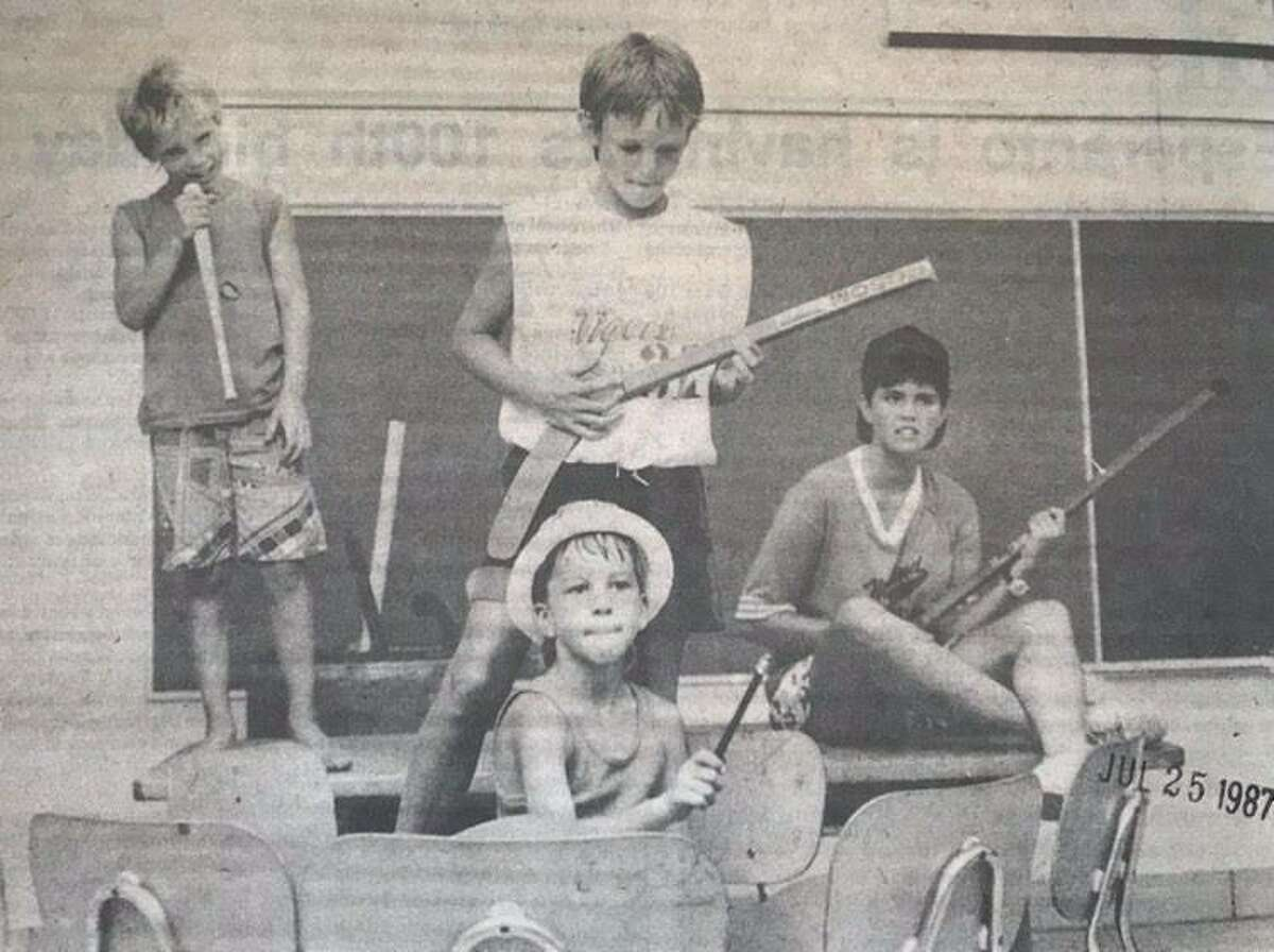 "Four mock musicians, Dan Lanning, 8, vocals; Jon Lanning, 9, lead guitar; Riley Olsen, 8, drums, and playground leader Kari Humphrey, rhythm guitar, play during Midland Parks and Recreation summer program ""Mock Rock Concert."" July 1987"
