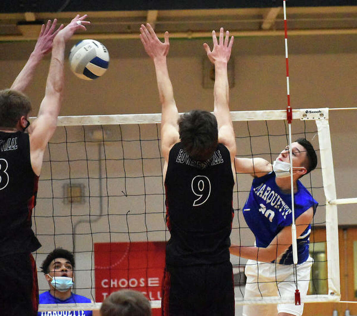 Marquette Catholic senior Jake Roth (right) hits past a double block put up by Edwardsville in a May 12 match at Lucco-Jackson Gym in Edwardsville. Roth is the 2021 Telegraph Boys Volleyball Player of the Year.