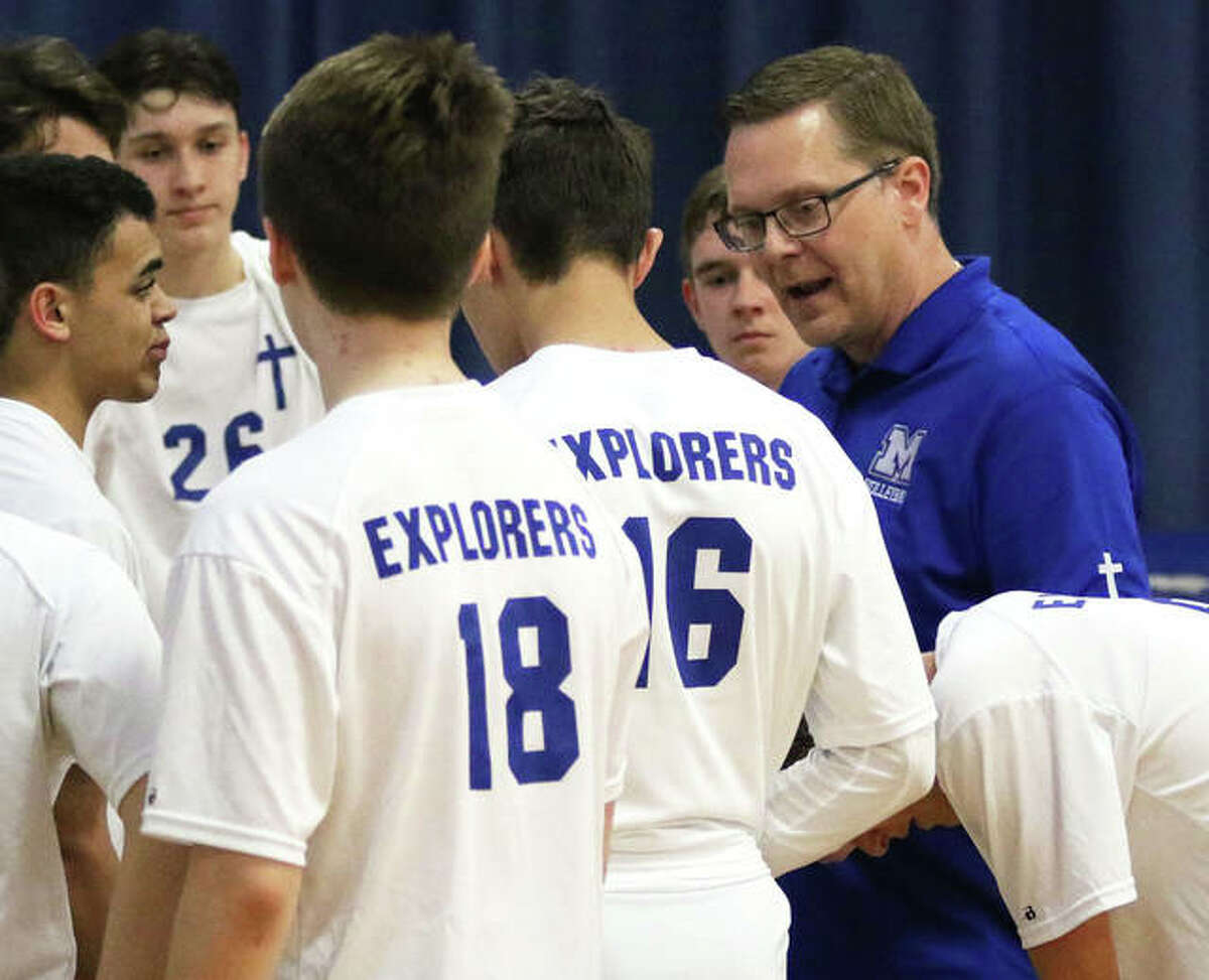 Marquette Catholic coach Mark Ellebracht (right) talks with his team during a match in 2019 when the Explorers played a junior varsity schedule. Marquette's first season as a varsity program ended with a 9-7 record and with Ellebracht as the 2021 Telegraph Boys Volleyball Coach of the Year.