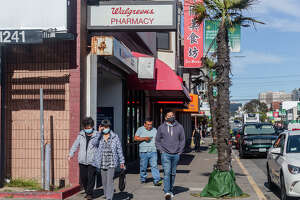 Masked customers and one unmasked exit Walgreens on Irving Street in the Outer Sunset on Monday afternoon, August 2, 2021. A new Bay Area indoor mask mandate goes into effect on Aug. 3, 2021.