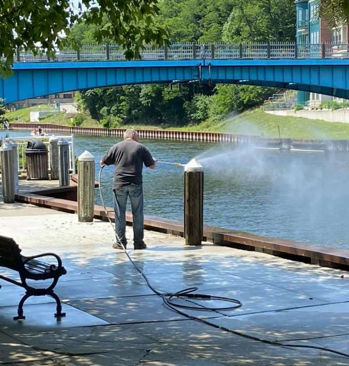 A Manistee Proud volunteer powerwashes a section of the Riverwalk. Organizers of the local civic group say they need more willing volunteers to get the job done.