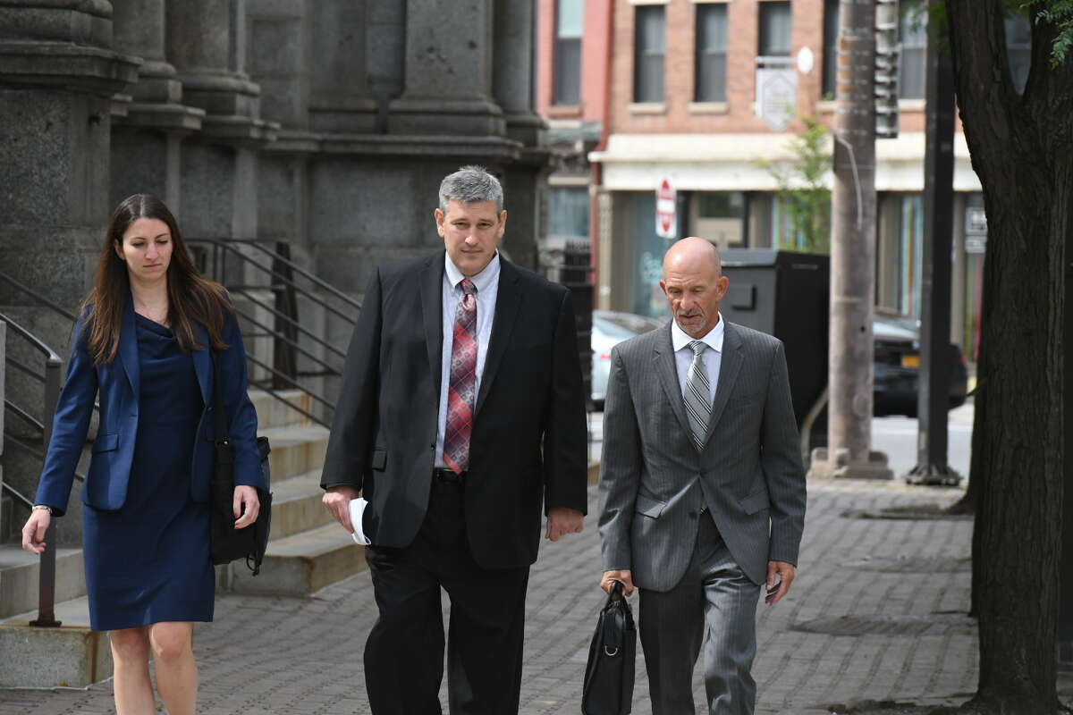 Former MyPayrollHR CEO Michael Mann, center, arrives at U.S. District Court with his attorneys to be sentenced in the $100 million fraud case that brought down his company.