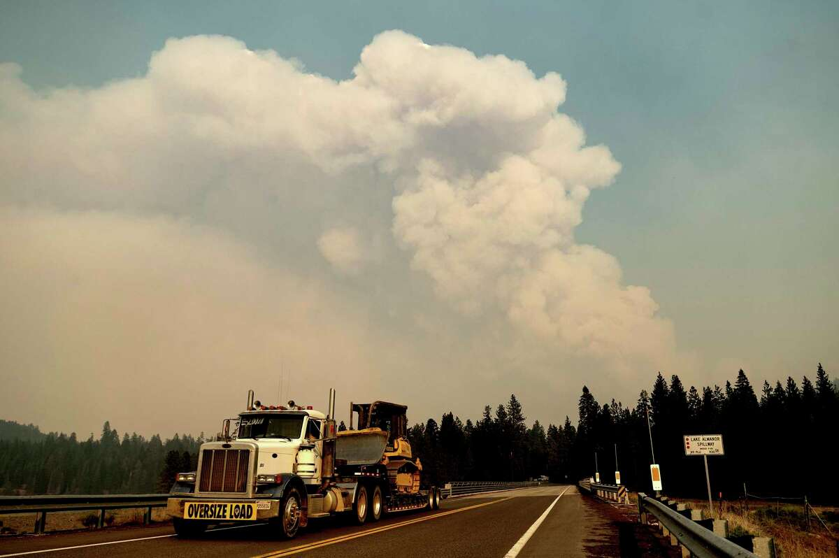 A smoke plume rises from the Dixie Fire as it approaches Lake Almanor in Plumas County, Calif., on Tuesday, Aug. 3, 2021. (AP Photo/Noah Berger)