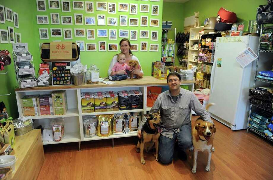 Lindsay and Justin Lancaster pose inside their store Pets Unleashed, with their daughter Olivia, 4 months, and three dogs Maya, on counter, Dylan, bottom left, and Charlie, at right, in Fairfield, Conn. on Wednesday September 15, 2010. Photo: Christian Abraham / Connecticut Post