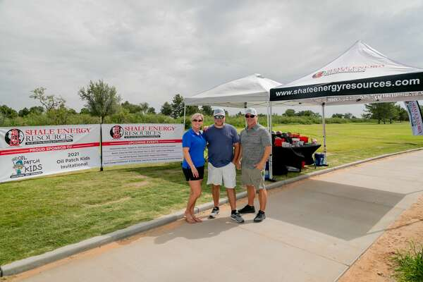 From left Miranda Kennedy, Jeff Kennedy and Arnie Alexander photographed at the title sponsor Shale Energy tent during the Oil Patch Kids golf tournament July 16, 2021 at Hogan Park Golf Course in Midland, Texas. Photo Credit: The Oilfield Photographer, Inc.