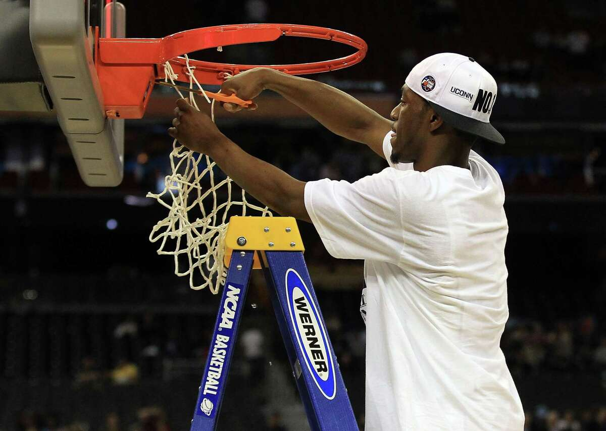 HOUSTON, TX - APRIL 04: Kemba Walker #15 of the Connecticut Huskies cuts down the net after defeating the Butler Bulldogs to win the National Championship Game of the 2011 NCAA Division I Men's Basketball Tournament by a score of 53-41 at Reliant Stadium on April 4, 2011 in Houston, Texas. (Photo by Streeter Lecka/Getty Images)