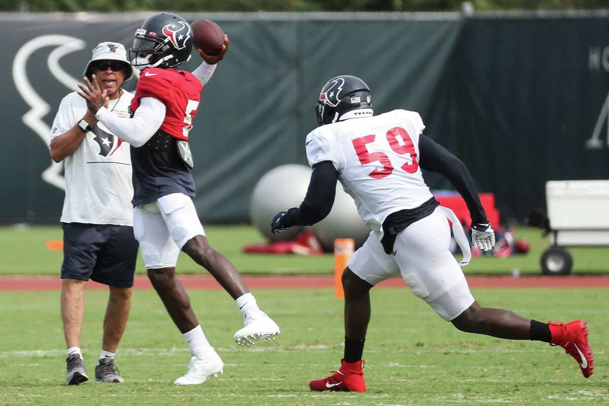 Houston Texans quarterback Tyrod Taylor (5) is chased by defensive end Whitney Mercilus (59) as he rolls out to pass during an NFL training camp football practice Wednesday, Aug. 4, 2021, in Houston.