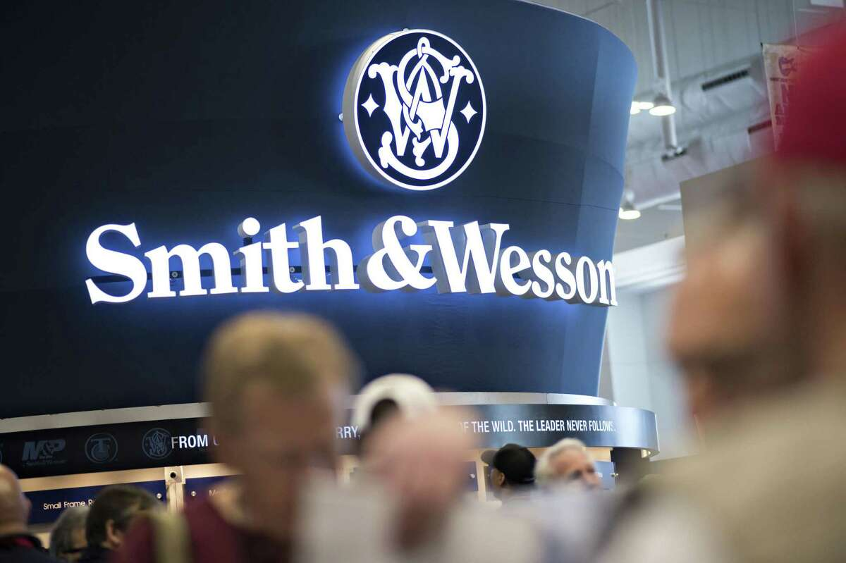Attendees look over hand guns in the Smith & Wesson booth at a National Rifle Association meetings at the Music City Center in Nashville, Tenn., on April 11, 2015.