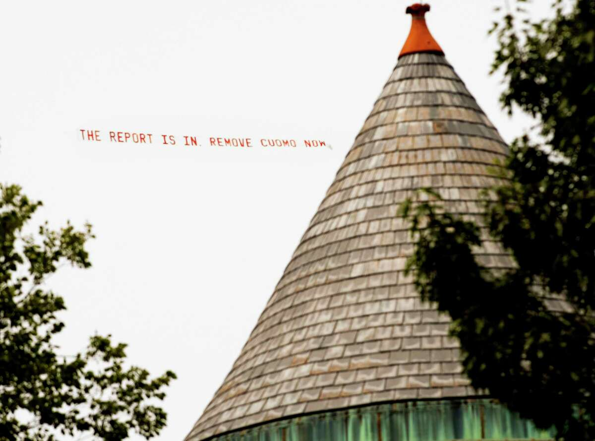 """A plane pulling a banner reading """"the report is in remove Cuomo now"""" is seen flying over the Governor's Mansion on Wednesday, Aug. 4, 2021 in Albany, N.Y."""