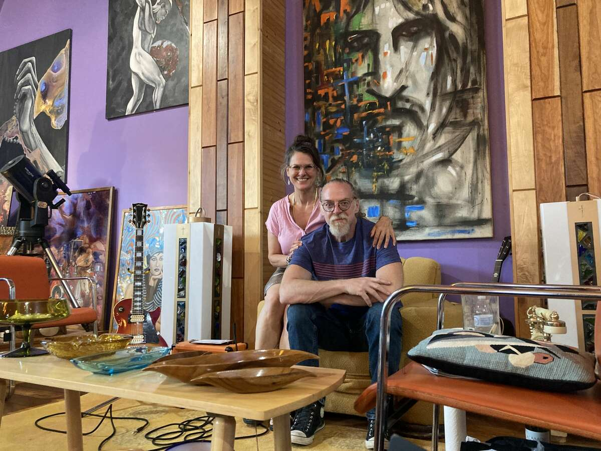 Carrie and Michael Zaitz pose in front of Michael's art at the forefront of the White Gallery Church. (Teresa Homsi/Huron Daily Tribune)