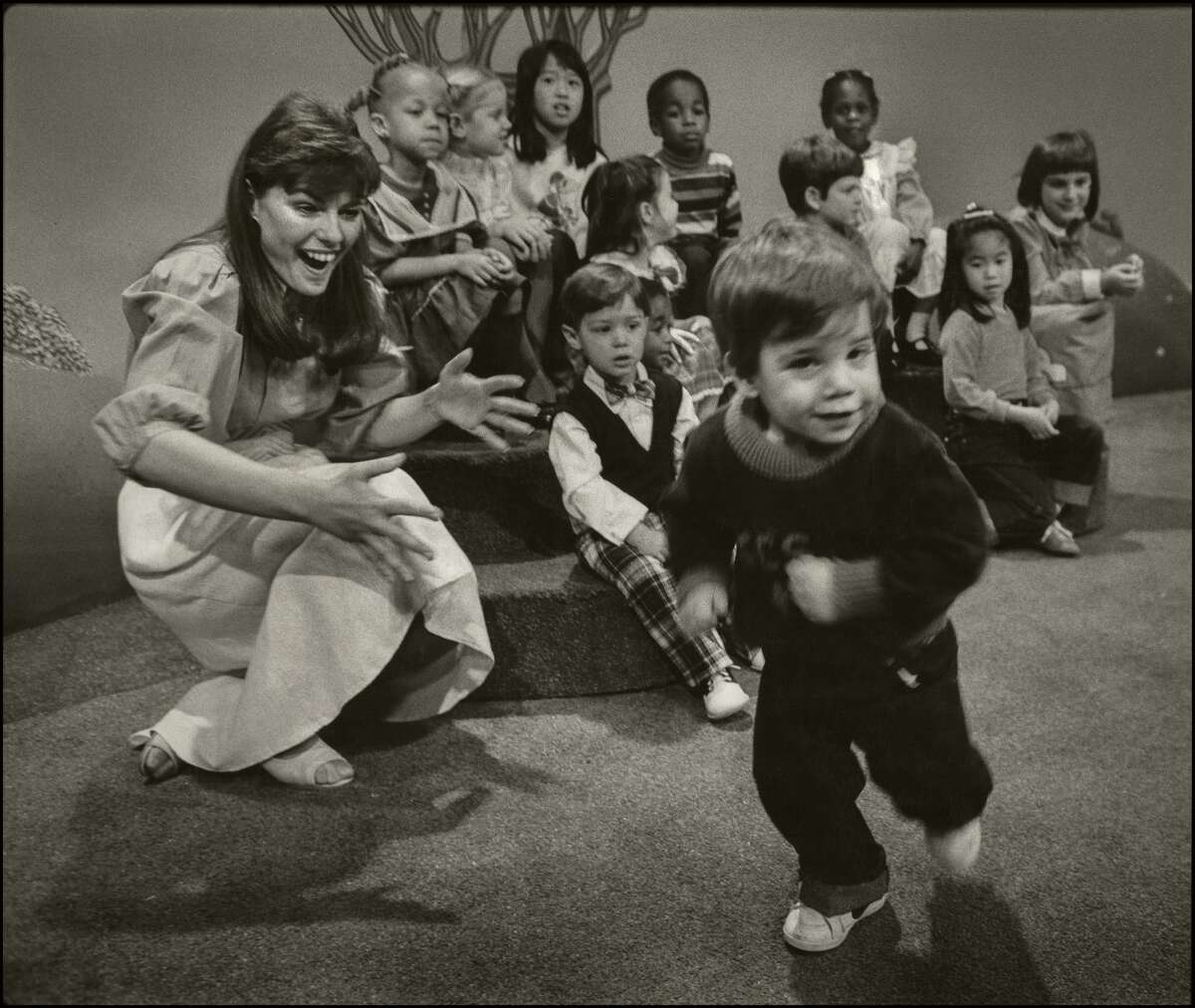 """Children's television host Nancy """"Miss Nancy"""" Besst laughs as a young boy runs past on the set of the TV show """"Romper Room"""" in Oakland in 1983."""