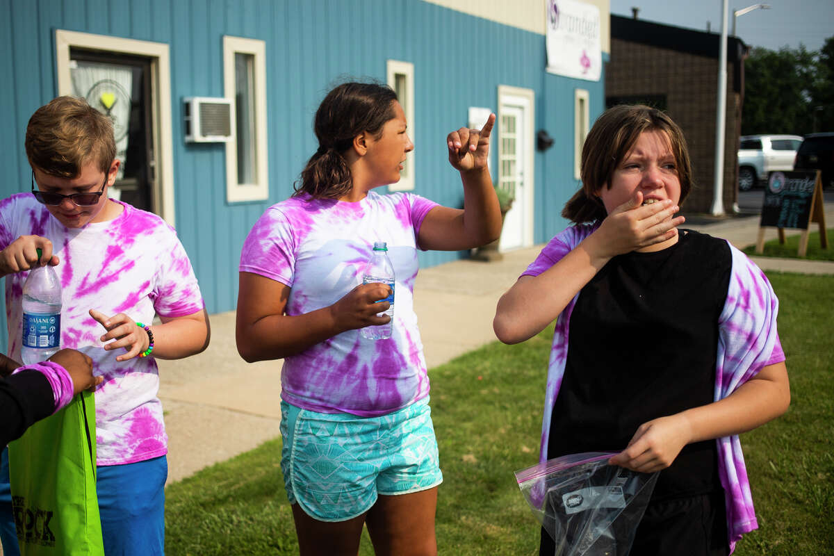 From left, Miles Evans, 12, Jaelynn Alvarez, 12, and Claire Cunningham, 13, all participants in The ROCK Teen Summer Camp, eat popcorn to get to a clue as they complete a scavenger hunt activity during The ROCK Amazing RaceSummer Camp Wednesday, Aug. 4, 2021 at Pop-Pop's Gourmet Popcorn in Midland. (Katy Kildee/kkildee@mdn.net)