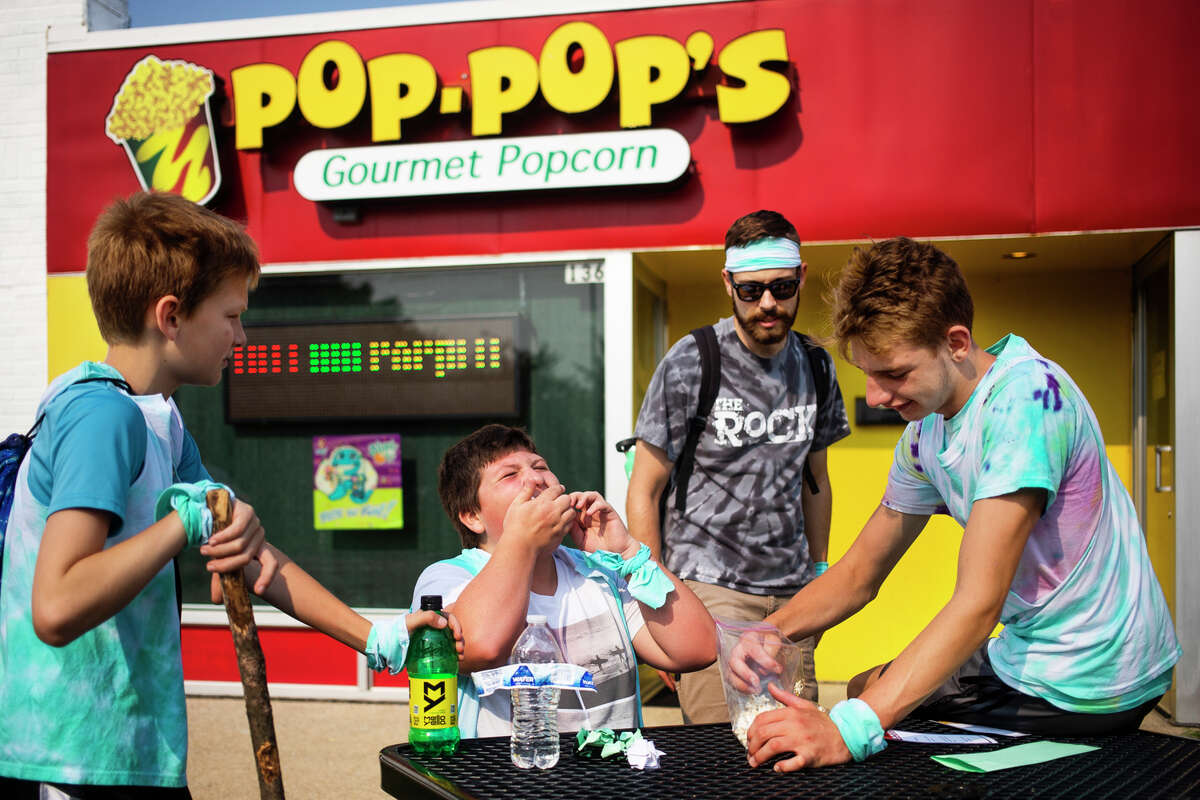 From left, Trent Provoast, 11, Zack Burger, 14, team lead Tyler Porter and Carter Mangapora, 15, eat popcorn to get to a clue as they complete a scavenger hunt activity during The ROCK Amazing RaceSummer Camp Wednesday, Aug. 4, 2021 at Pop-Pop's Gourmet Popcorn in Midland. (Katy Kildee/kkildee@mdn.net)