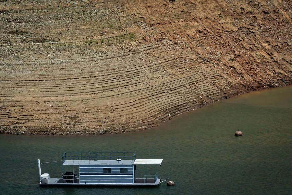 A houseboat floats near the shoreline which has been striated by the receding water level at the Bidwell Canyon Marina at Lake Oroville in Oroville, Calif. Lake Oroville dried up to levels not seen in decades due to California's exceptional drought.