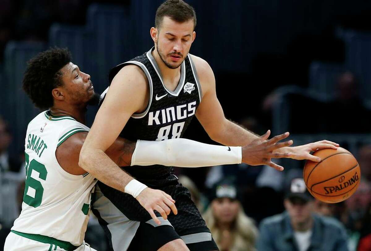 Boston Celtics' Marcus Smart, left, reaches in to try to steal the ball from Sacramento Kings' Nemanja Bjelica during the second quarter of an NBA basketball game Monday, Nov. 25, 2019, in Boston. (AP Photo/Winslow Townson)