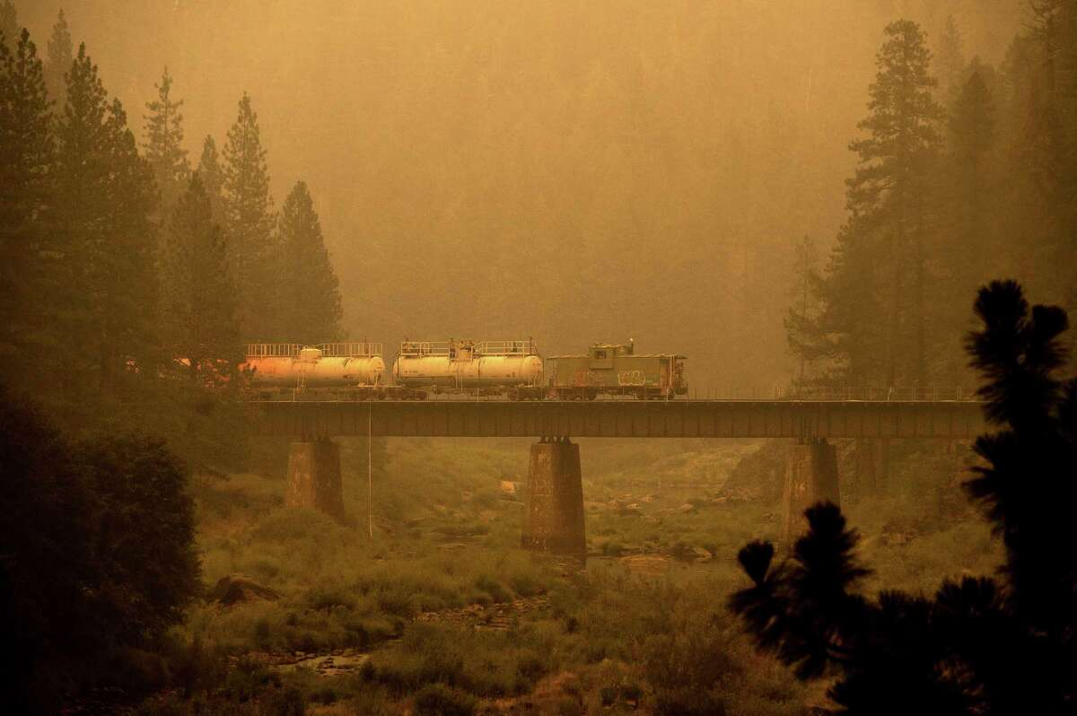 A fire train crosses a bridge as the Dixie Fire burns in Plumas County, Calif., on Saturday, July 24, 2021.