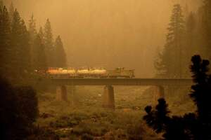 A fire train crosses a bridge as the Dixie Fire burns in Plumas County, Calif., on Saturday, July 24, 2021. The train is capable of spraying retardant to coat tracks and surrounding land.