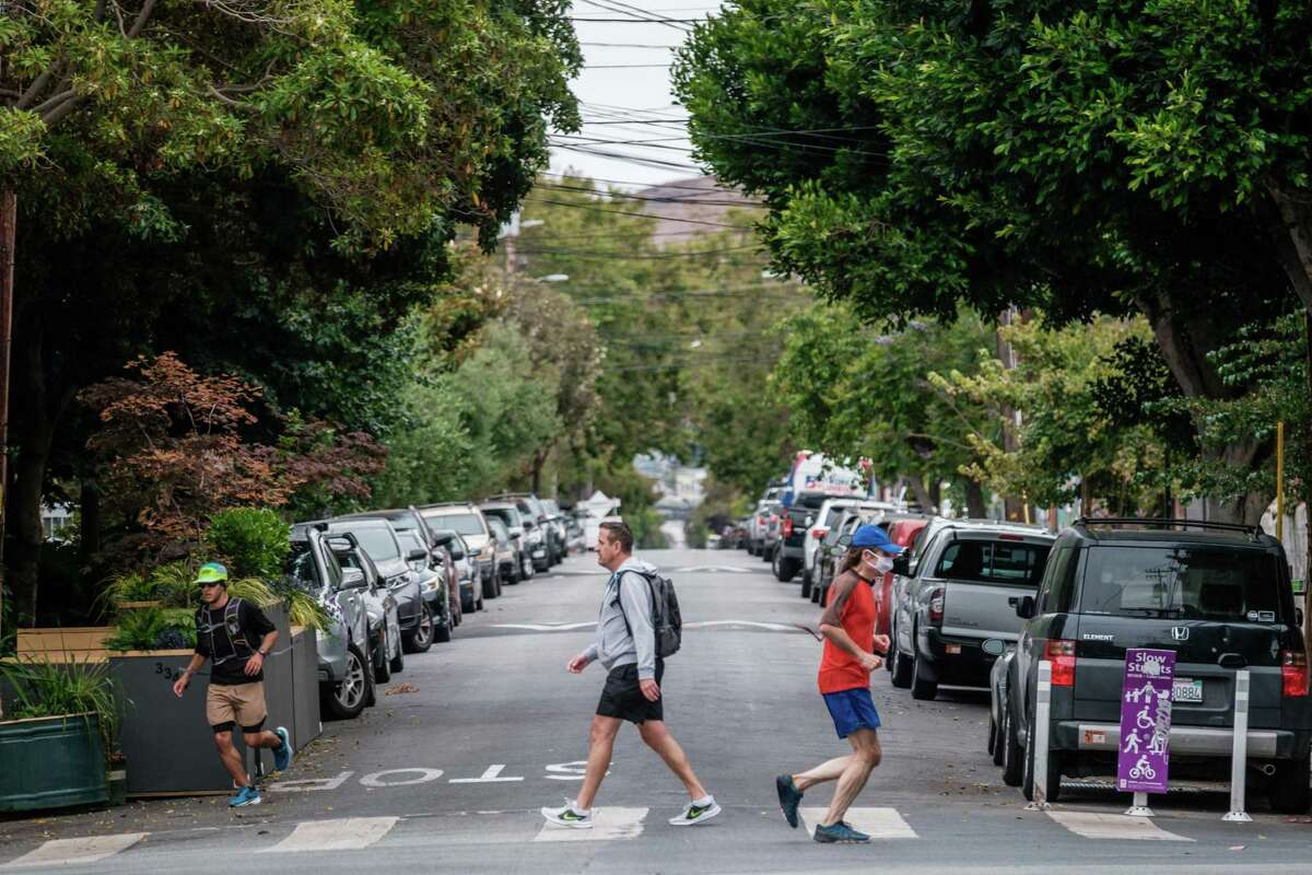 Pedestrians and joggers are seen on Shotwell Street in San Francisco on Wednesday. The SFMTA approved the first round of Slow Streets to make it beyond the city's emergency COVID-19 order. Shotwell Street in the Mission District between 14th Street and Cesar Chavez Street, is among the four.
