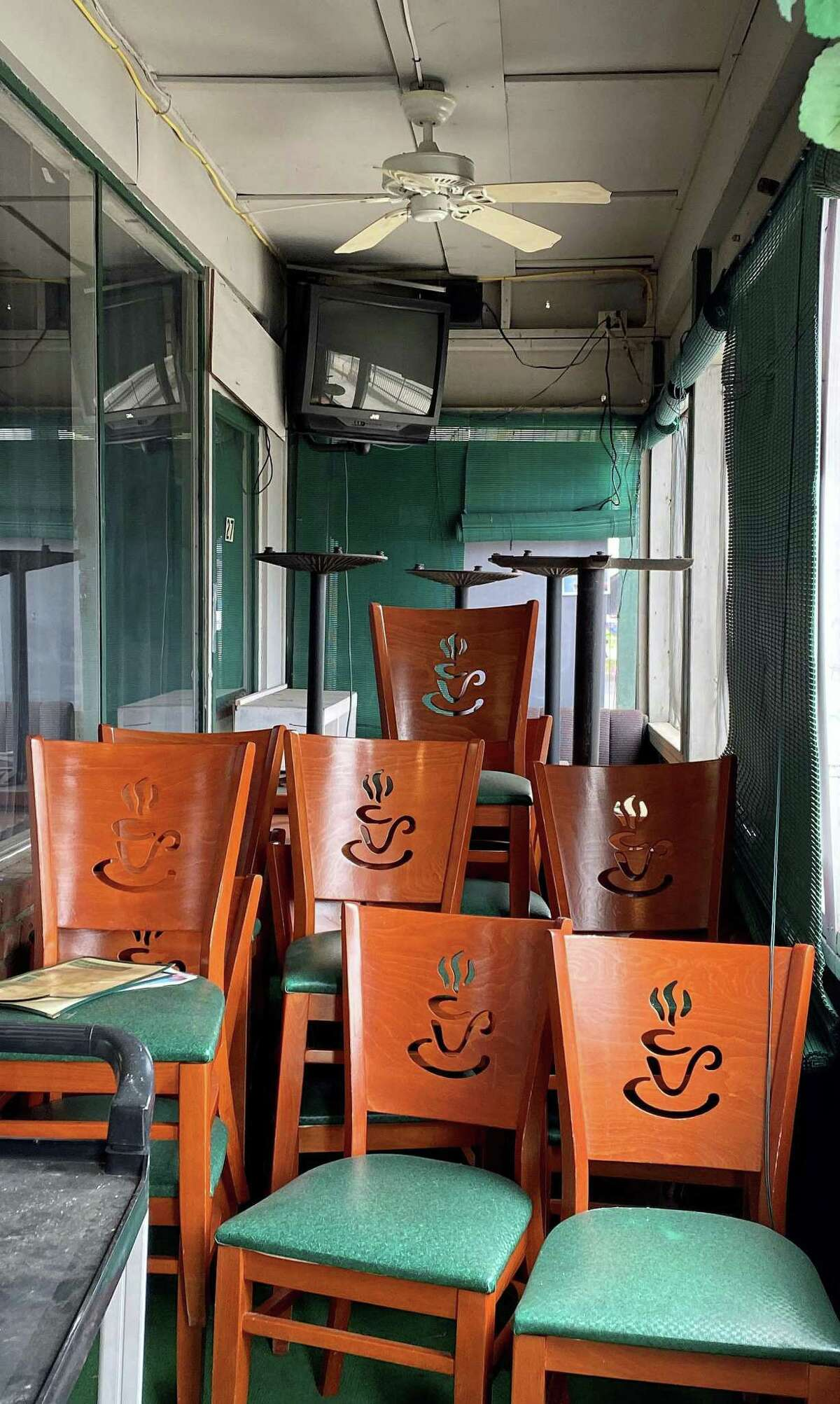 """Chairs are stacked inside the """"porch,"""" which the owners of The Coffee Break in Clinton will open up to an outside covered patio area."""