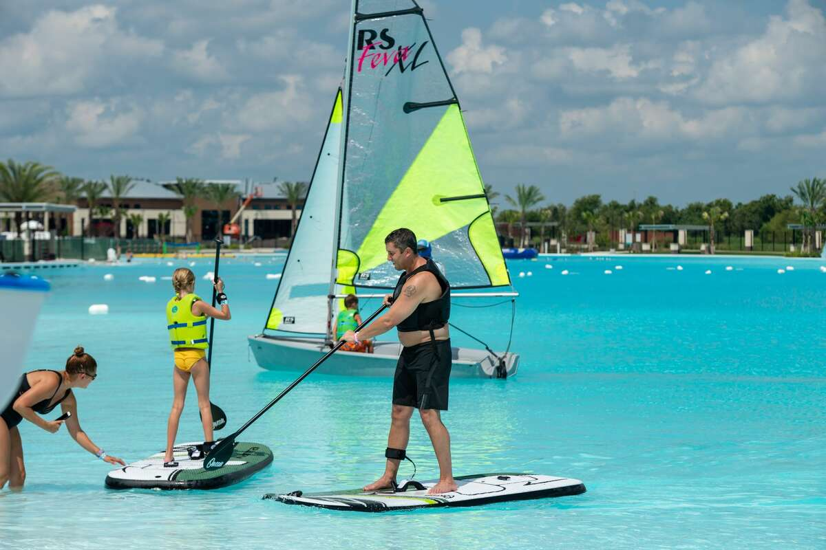 Stand-up paddle boarders test the waters of the National Sailing Club at Lago Mar. The club offers members and nonmembers access to sailboats, single and tandem kayaks and an electric boat that seats 12.