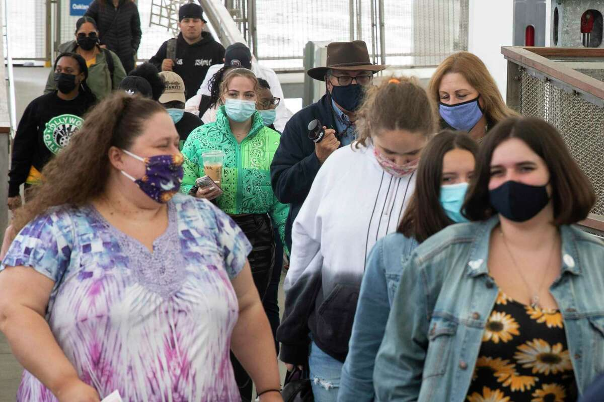 Commuters wear masks while exiting a ferry boat from Vallejo at the ferry terminal in San Francisco, Calif. Tuesday, July 6, 2021.