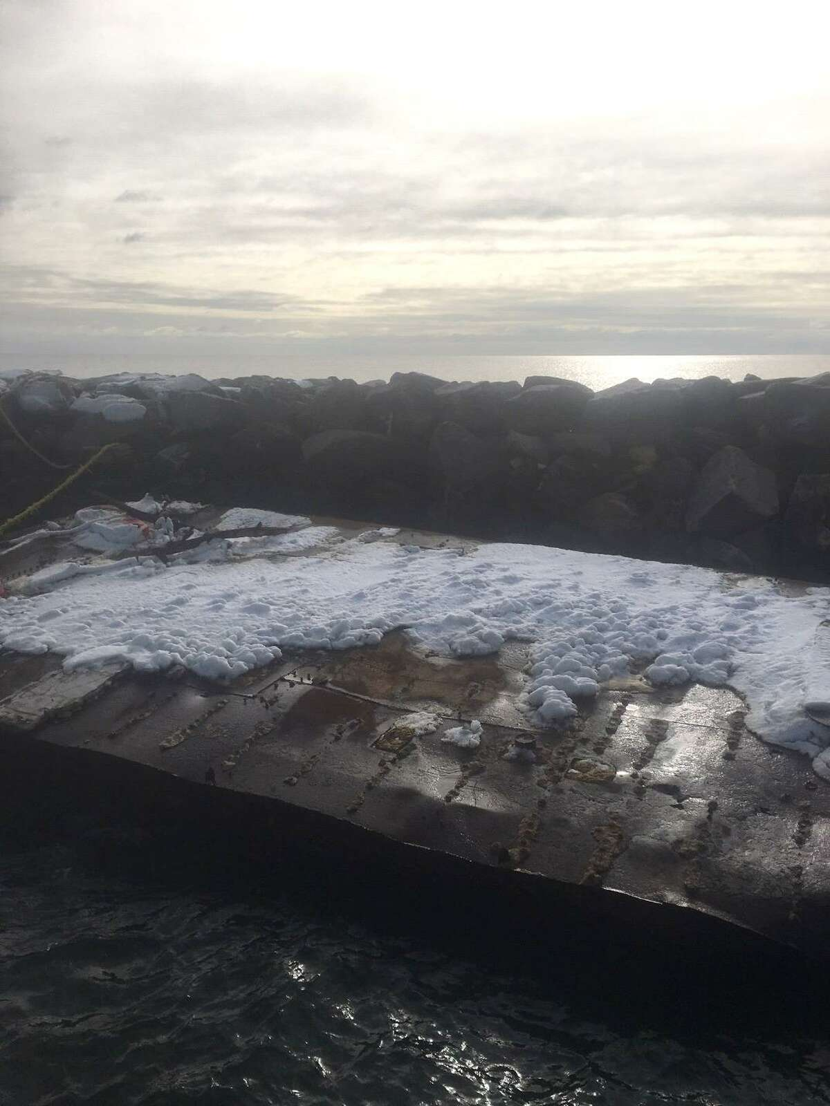 A barge tied to the breakwater at Lighthouse Point Park after drifting from English Station in the Mill River, photographed in January 2021.