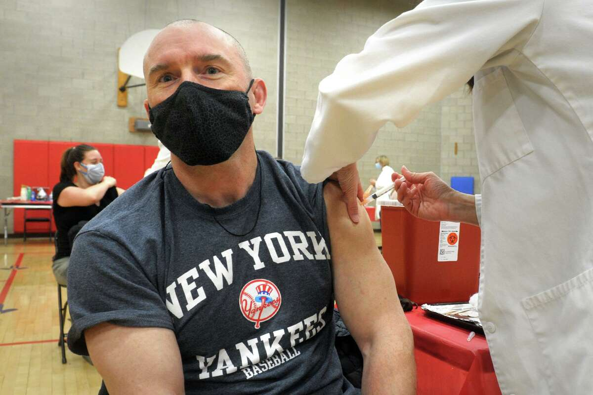 Chris Varcoe, a teacher from Roger Ludlowe Middle School, in Fairfield, receives a COVID-19 vaccination at the Bigelow Center clinic in Fairfield, Conn. March 1, 2021.
