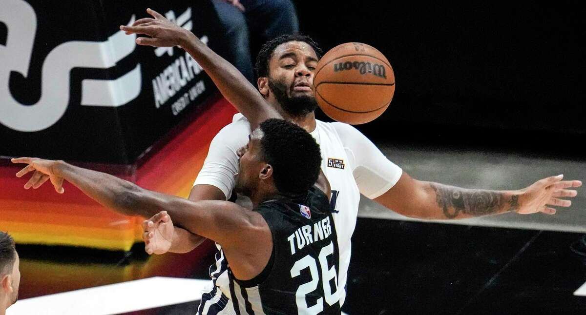 Spurs guard Justin Turner (26) and Utah Jazz forward Juwan Morgan, top, collide under the net during an NBA summer league basketball game Tuesday, Aug. 3, 2021, in Salt Lake City.