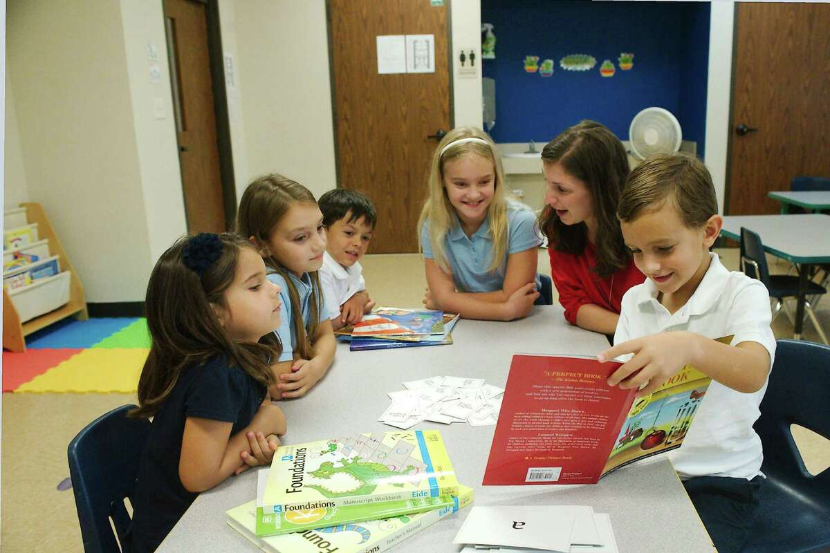 Deep Waters Academy Head of School Amelia Chiara sits with Gianna Chiara, left, Avila Fontana, Oliver Czar and Marie Fontana as Francis Fontana reads. The new academy is part of University-Model Schools, a Christian college-preparatory education system that combines elements of home schooling and private school
