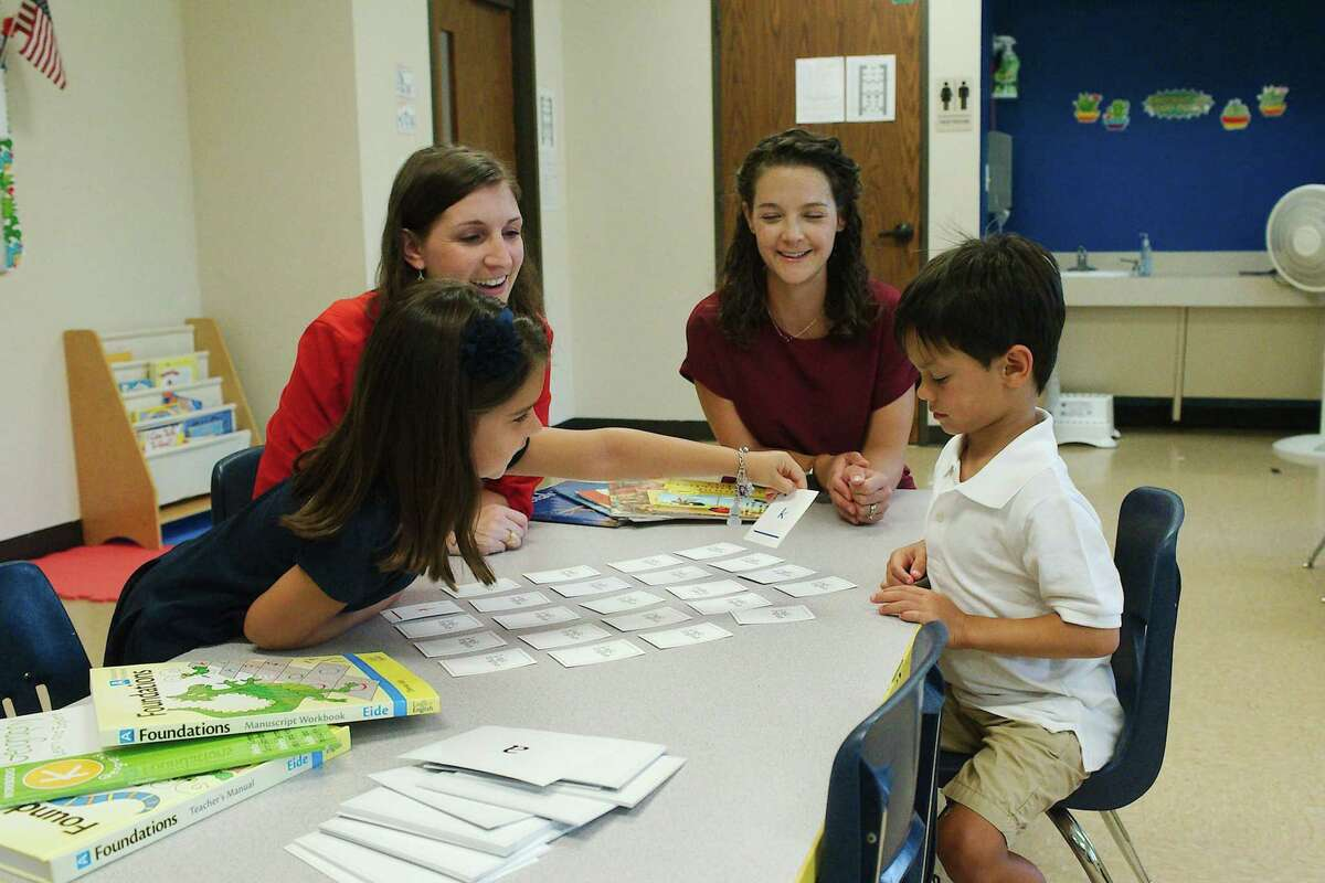 Amelia Chiara and her daughter Gianna, left, sit with Kira Czar and her son Oliver while the children are introduced to some of the activities they will do in class and at home.