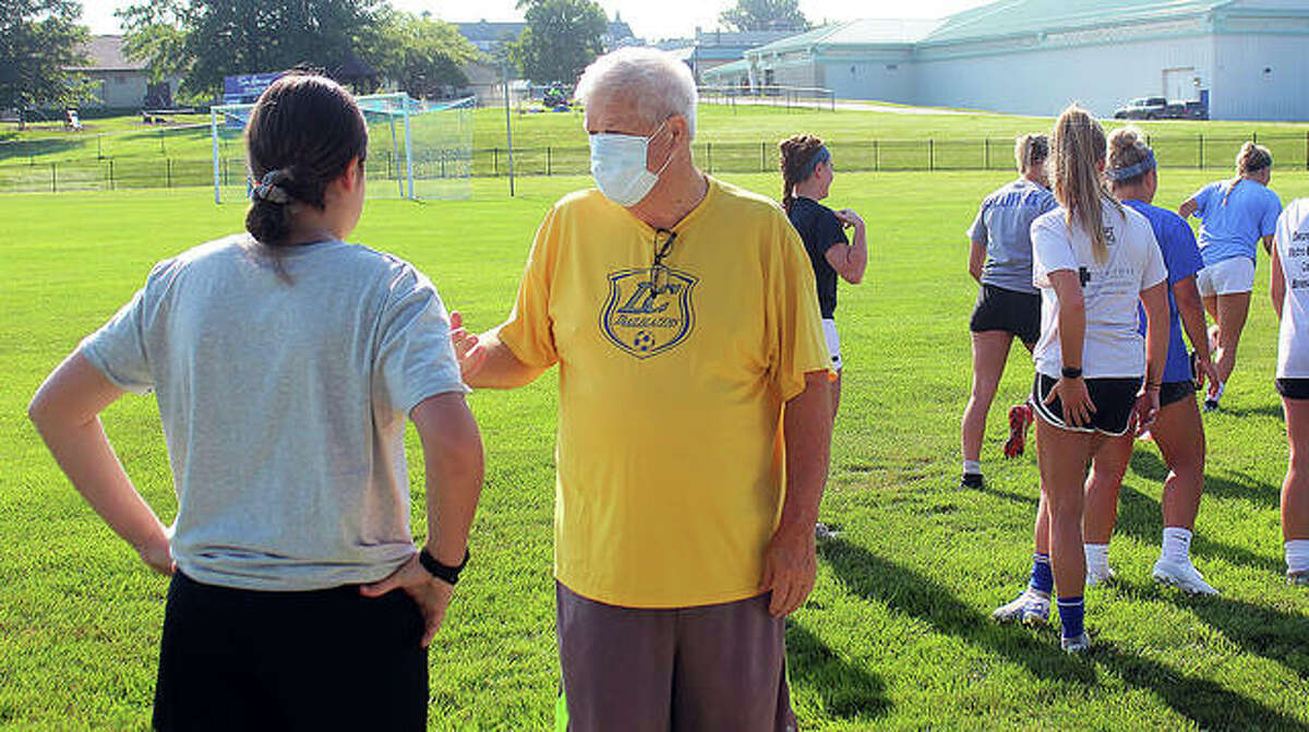 Lewis and Clark Community College women's soccer coach Tim Rooney, right, speaks with Lauren Kirby, left, a freshman center back from Australia, during the Trailblazers' first preseason practiceWednesday morning at LCCC.