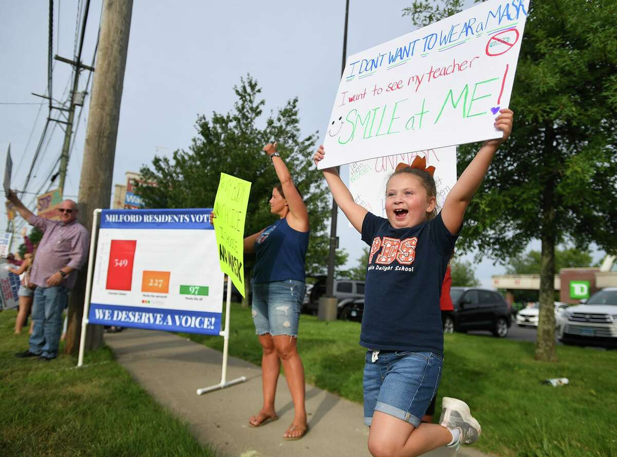 Lucia Andrews, 6, right, of Milford, enthusiastically participates in an Unmask Our Kids rally on the Post Road in Milford, Conn. on Tuesday, August 3, 2021. The rally was organized by the Facebook group's Milford chapter.