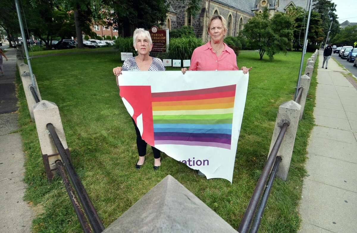 Lynne Lane, President of Unitarian Universalist Congregation's Board of Trustees, and Janis Stahlhut, member and the church's communication coordinator, at right, pose together with what remains of a Pride banner that was vandalized in Stamford, Conn., on Wednesday August 4, 2021. The banner, which hung in the pictured corner of the church grounds, was ripped away last Sunday.