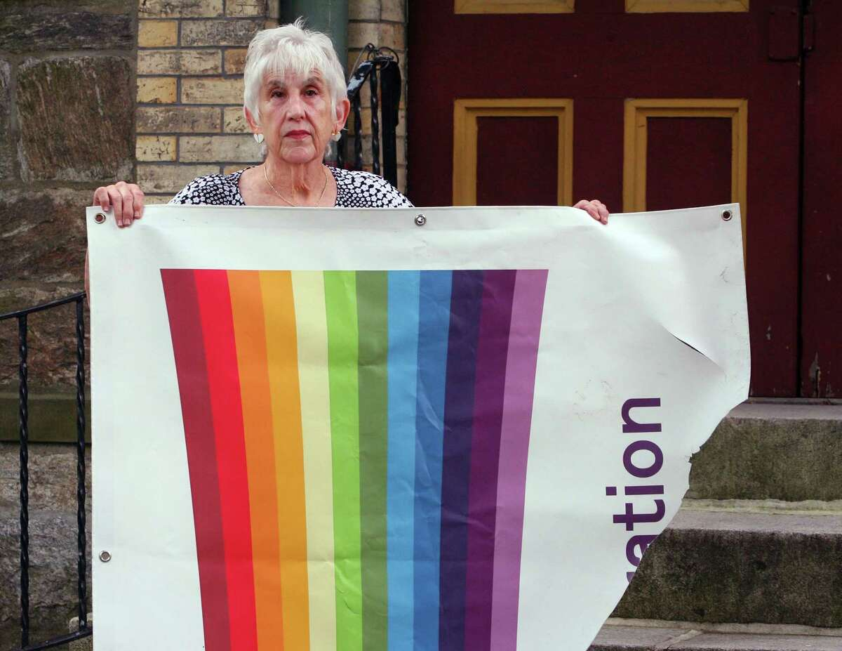 Lynne Lane, President of Unitarian Universalist Congregation's Board of Trustees, holds what remains of a Pride banner that was vandalized in Stamford, Conn., on Wednesday August 4, 2021. The banner, which hung in a corner of the church grounds, was ripped away last Sunday.