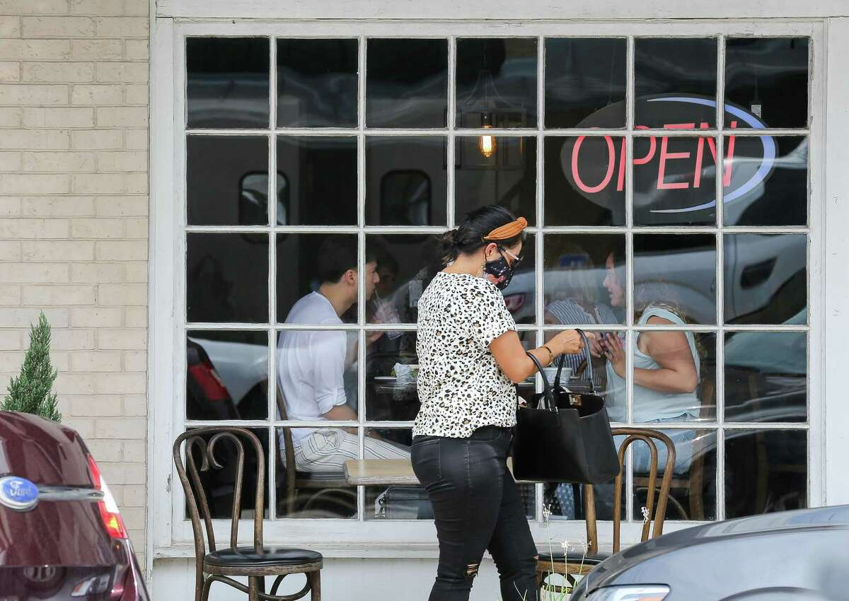 A woman wears a face mask before entering a restaurant on Tuesday, Aug. 3, 2021, in Richmond. 12,000 eligible Texas restaurants still wait for their grants.