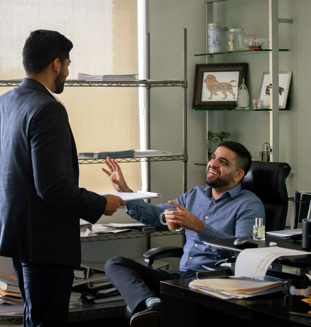Zulifiqar Abedin, right, talks with Kevin Gandhi, left, in Abedin's office, Wednesday, Aug. 4, 2021, at ZT Corporate's Houston office. The company's CEO, Taseer Badar, is pushing to require 100% of his employees to be vaccinated.