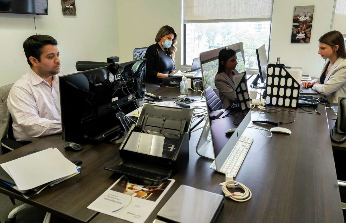 (LtoR) Sadiq Wahid, Giovanna Garcia and Guilia Avoltini work in their office, Wednesday, Aug. 4, 2021, at ZT Corporate's Houston office. The company's CEO, Taseer Badar, is pushing to require 100% of his employees to be vaccinated.