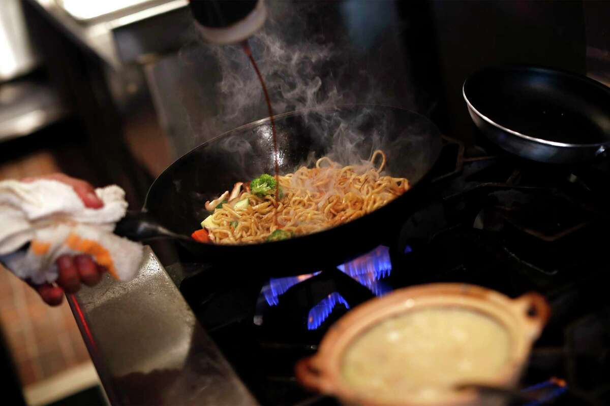 Chef Rob Lam prepares Shanghai vegetarian garlic noodles at Lily on Clement Street.