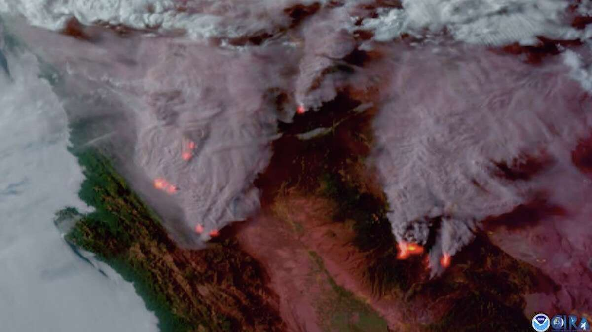 This screenshot of satellite video captured by the National Oceanic and Atmospheric Administration's GOES-17 satellite hovering 22,300 miles in space shows massive plumes of smoke and heat signatures from the wildfires blazing in Northern California.