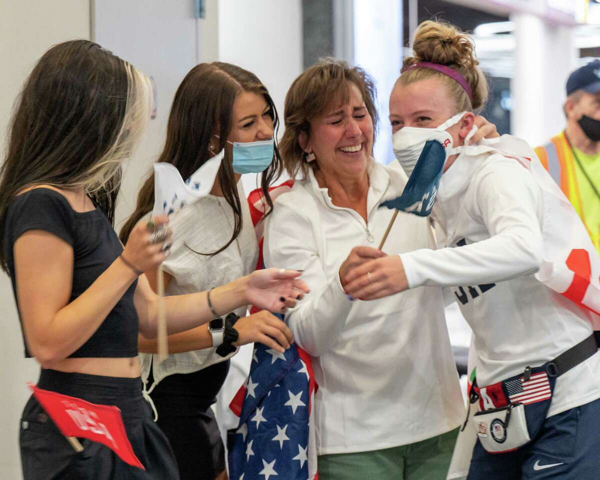 Emma White (right) is greeted by her mom, Chris White, and her sisters, Anna and Sarah, at the Albany International Airport on Wednesday, Aug. 4, 2021, after winning a bronze in the cycling team pursuit in the Tokyo Olympics. (Jim Franco/Special to the Times Union)