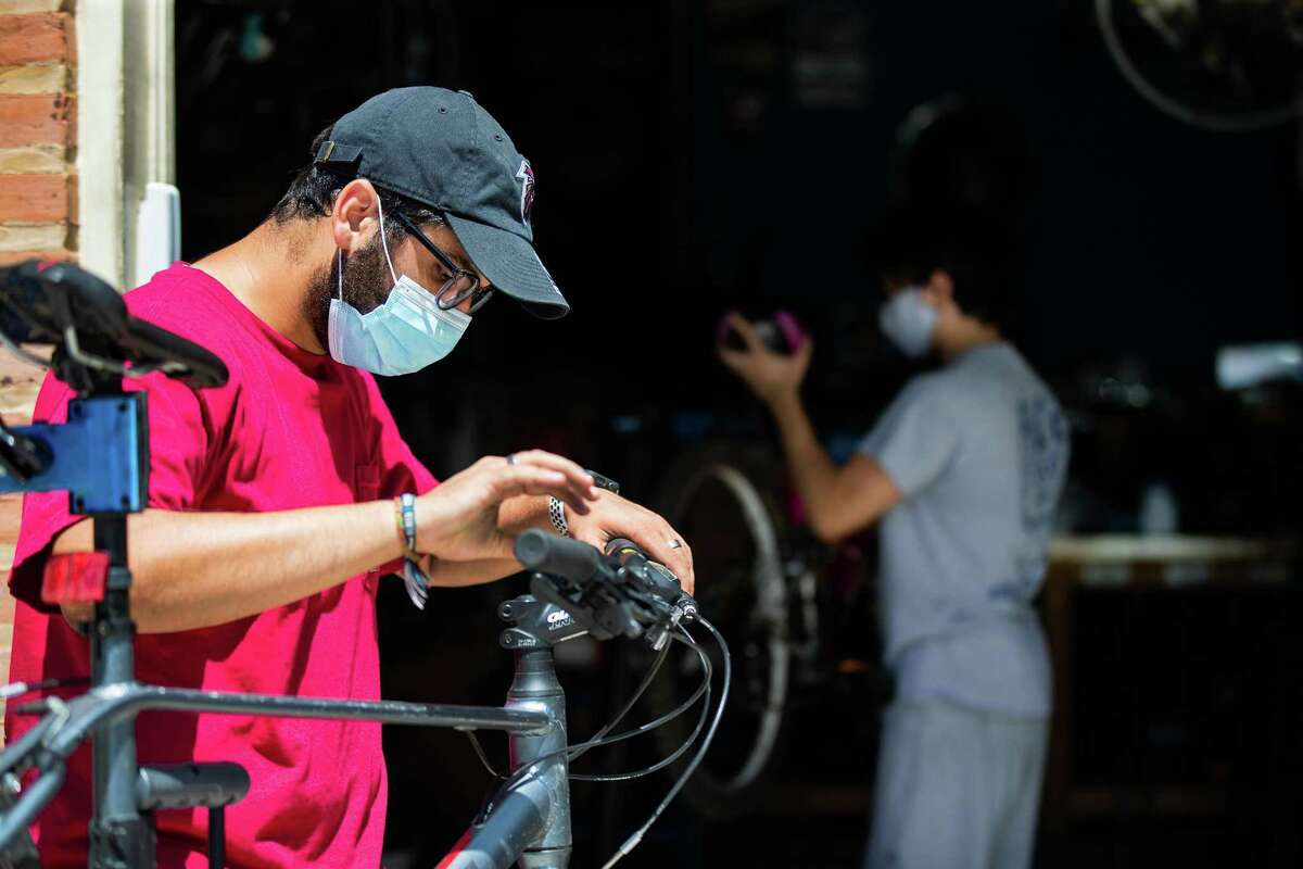 Rice University Rice Bikes' mechanic Danny Moloo, 19, works on a bicycle while wearing a mask, Monday, April 26, 2021, in Houston.