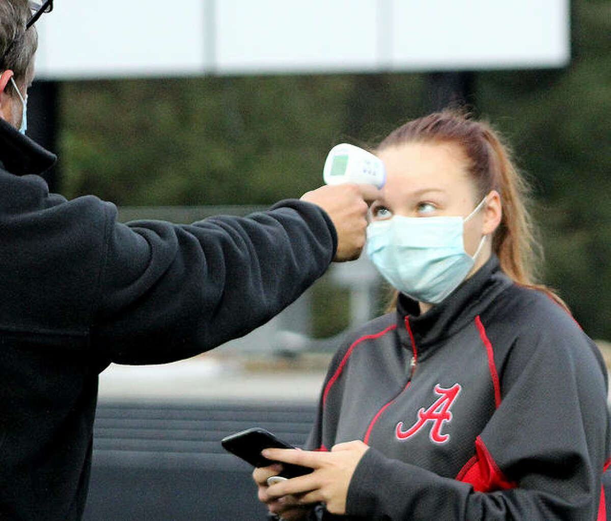 Alton soccer player Addison Miller has her temperature checked as part of the coronavirus protocol prior to a practice session last spring. On Wednesday evening, the Illinois High School association said it will require masks for all athletes participating this fall in indoor sports, including practices. Swimmers and divers will not have to wear masks during competition, but will be required to wear them when they are not competing.