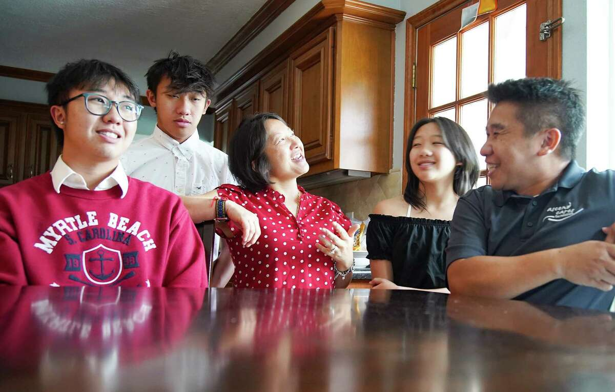 Za Moua center, who is Hmong American, talks about how proud the family is about Suni Lee's gold medal win at the Olympics and the interest it brought to Hmong culture with her family: Somchay Xiong, 21, from left, Kenshin, 18, Fayelin, 13, and husband Xiong Xiong at their Jersey Village home on Wednesday, Aug. 4, 2021.