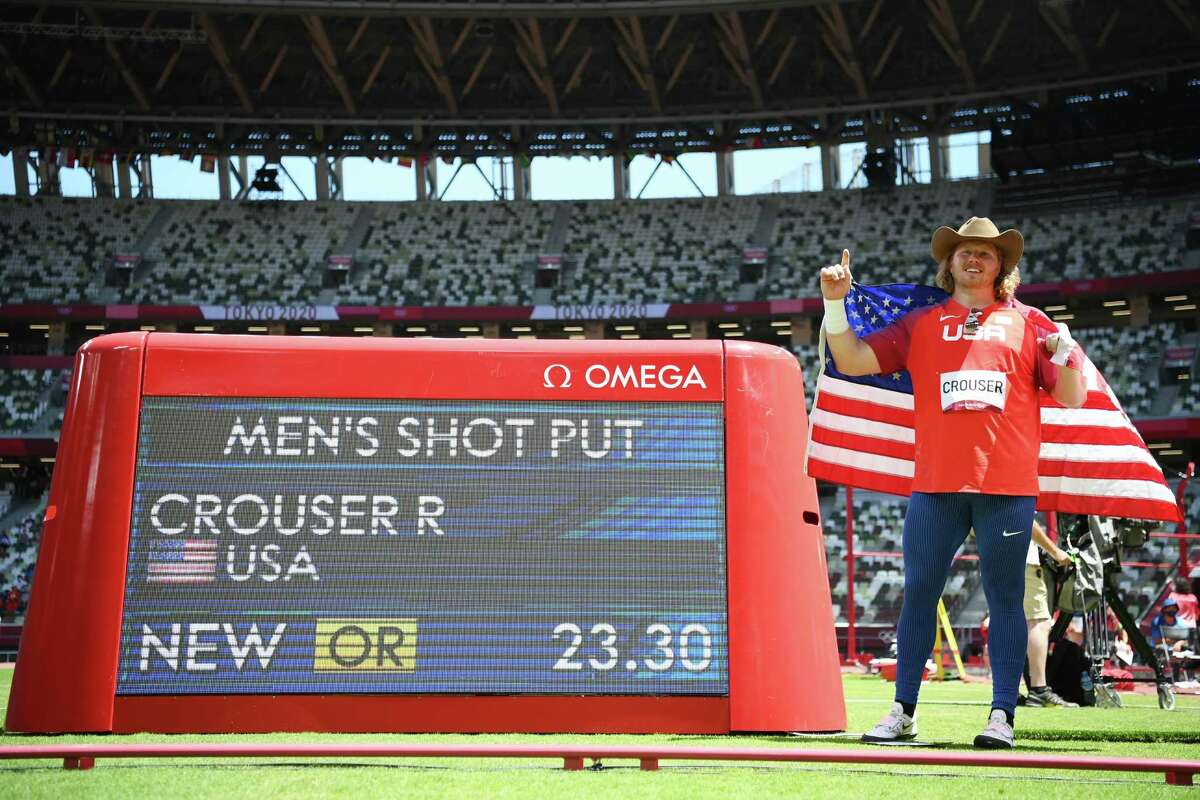TOKYO, JAPAN - AUGUST 05: Ryan Crouser of Team United States poses with a scoreboard showing his 23.30 throw for a new Olympic record in the Men's Shot Put Final on day thirteen of the Tokyo 2020 Olympic Games at Olympic Stadium on August 05, 2021 in Tokyo, Japan.